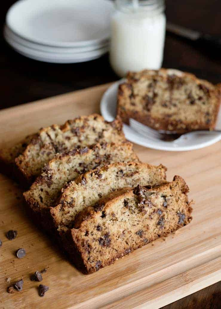 Banana Bread slices on a cutting boards with chocolate chips scattered