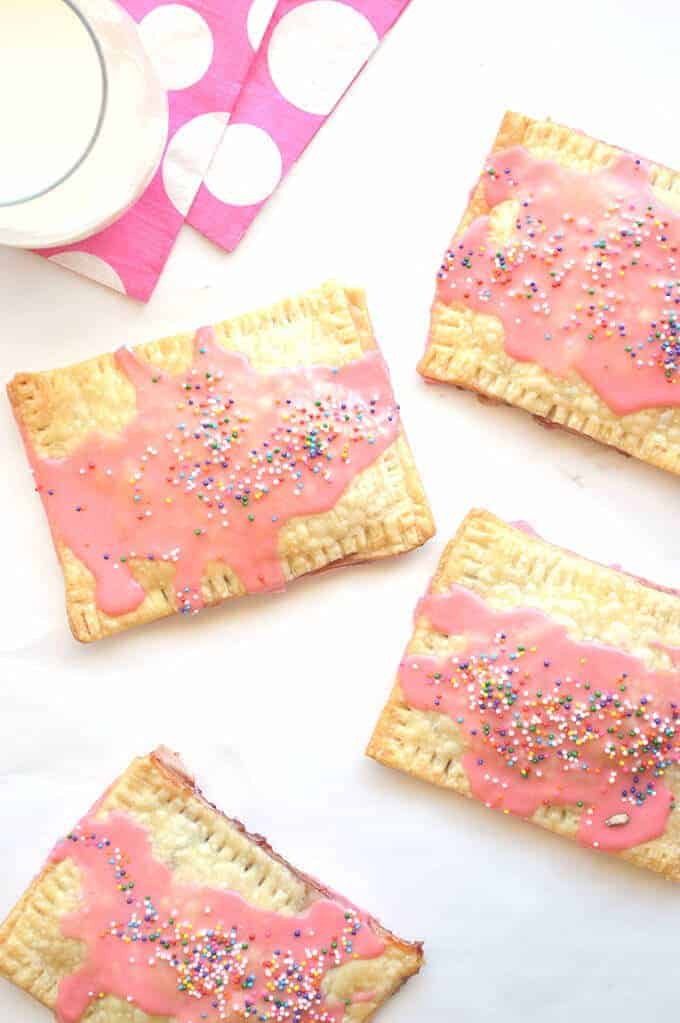 4 pink frosted strawberry pop tarts with rainbow sprinkles on a table