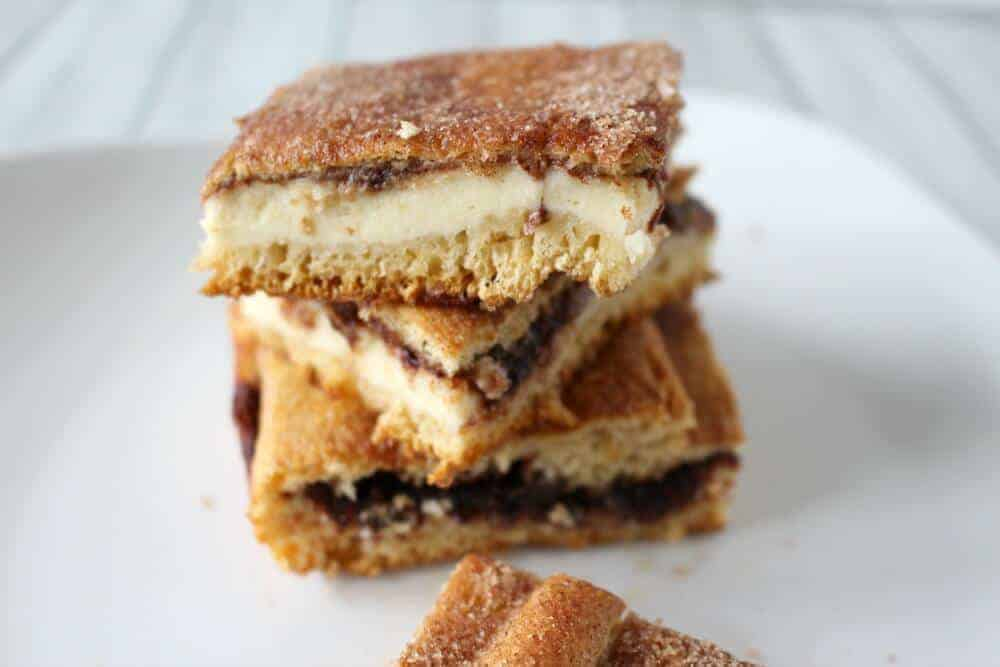 Cheesecake bars stacked on a white plate