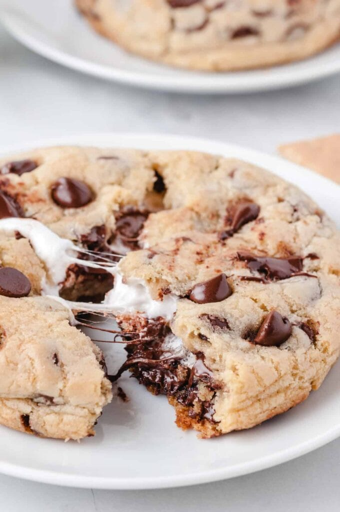 big chocolate chip cookie with marshmallow broken open on a white plate