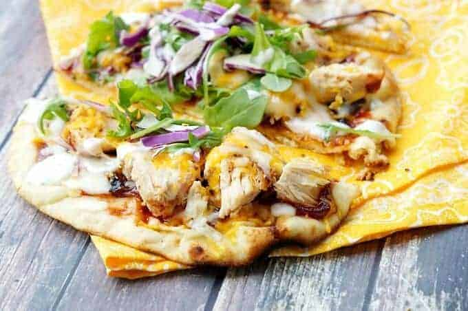 Grilled BBQ Chicken Flatbreads ingredients bbq sauce, gouda and cheddar cheeses, and caramelized onions.