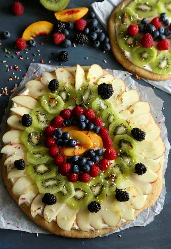This Sugar Cookie Fruit Pizza is not only delicious to eat, but it's fun to make and makes a great project for kids. They'll love adding all the toppings!