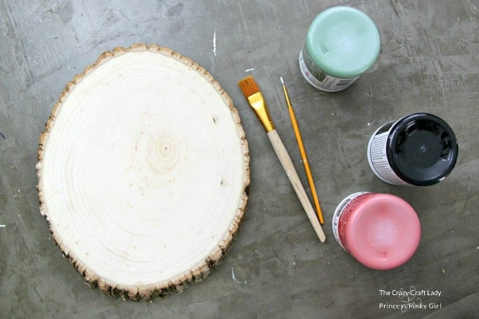 Materials needed to make a Wood Slice Painted Wreath - chalkboard paint, paint brushes and a wood round