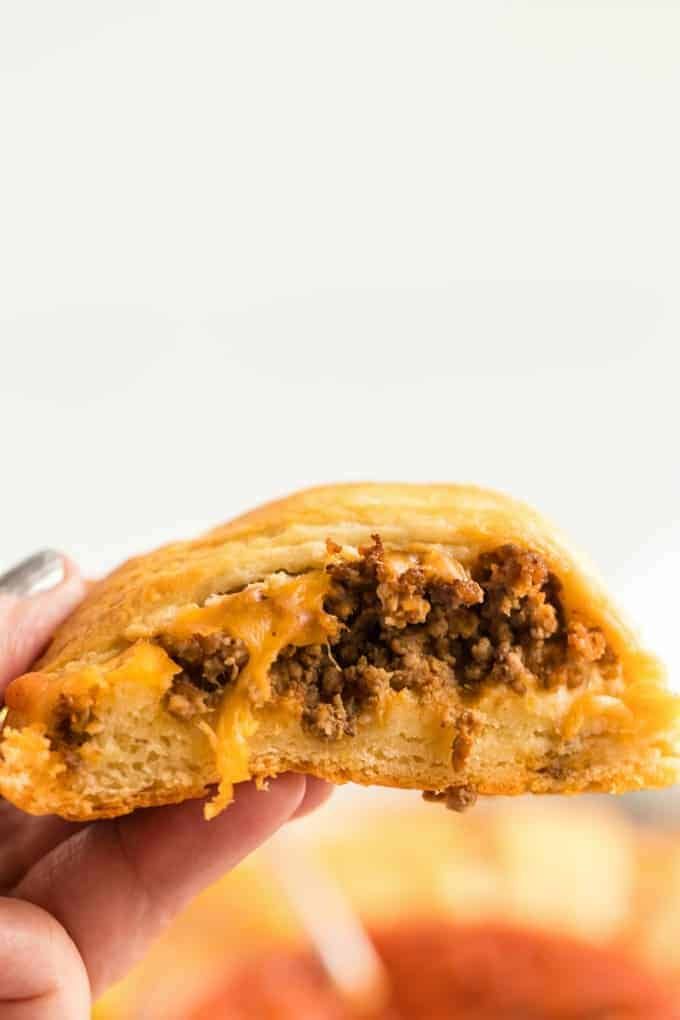 Piece of beef taco ring being held with cheese and beef coming out