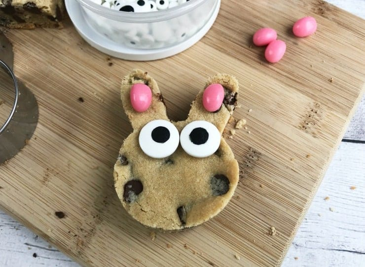 Attach candy eyes and ears to the cookie