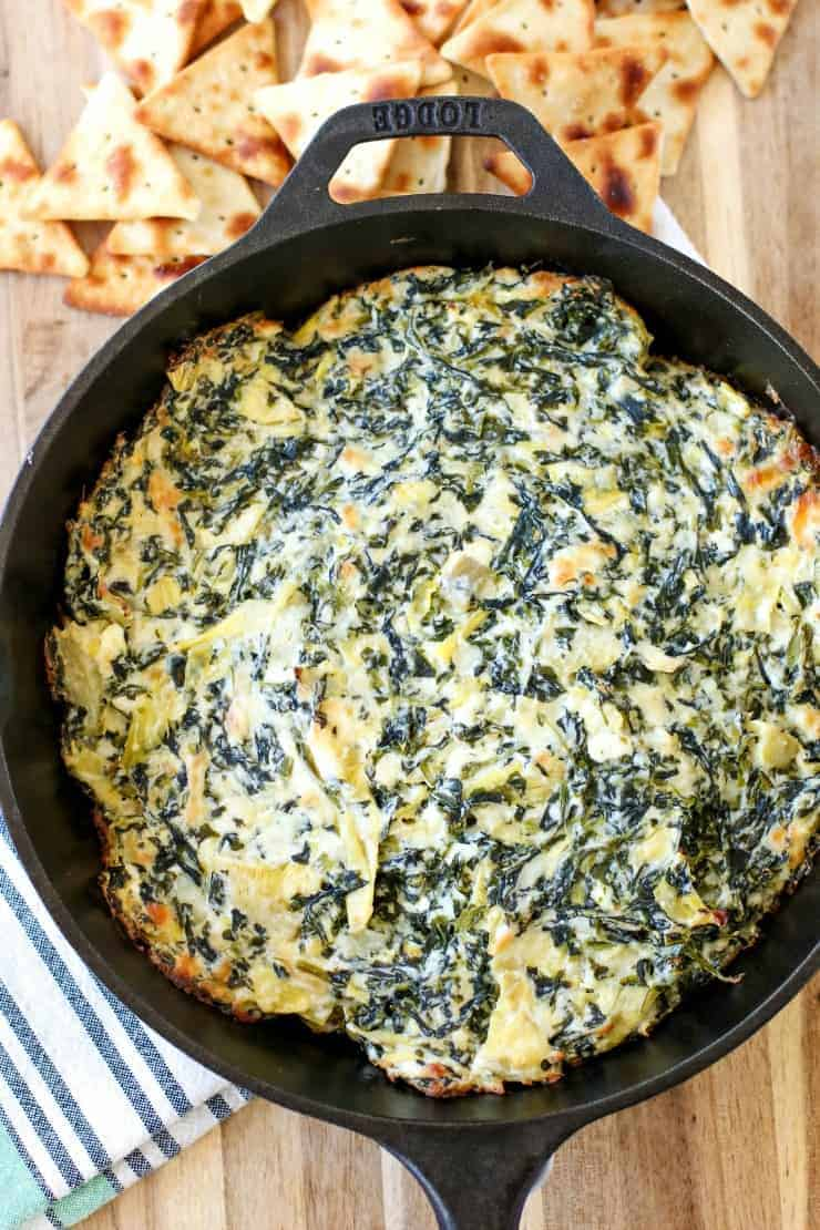 Spinach and artichoke dip in a black cast iron pan with dipping chips