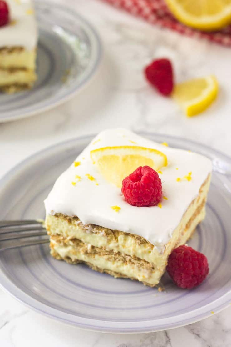 Lemon icebox cake on a grey plate with raspberries