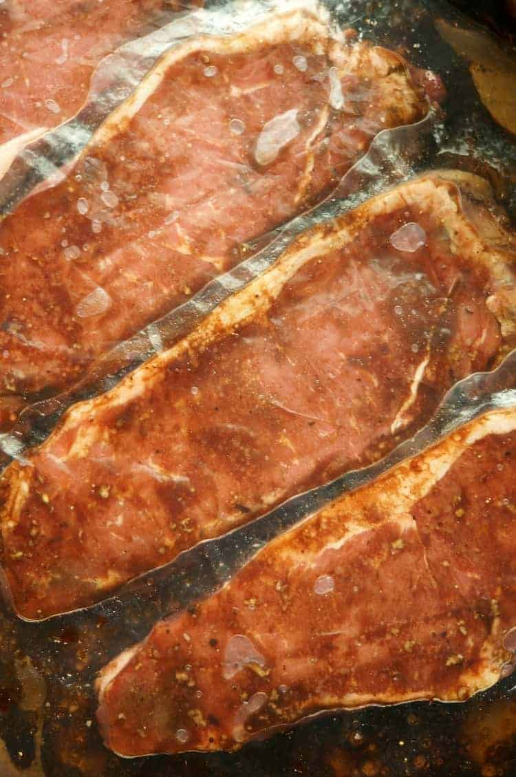 steaks marinating in a bag