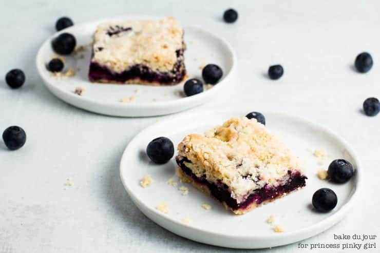 Blueberry Crumble Bars - Two Blueberry Crumb Bars, each one on a small white dish