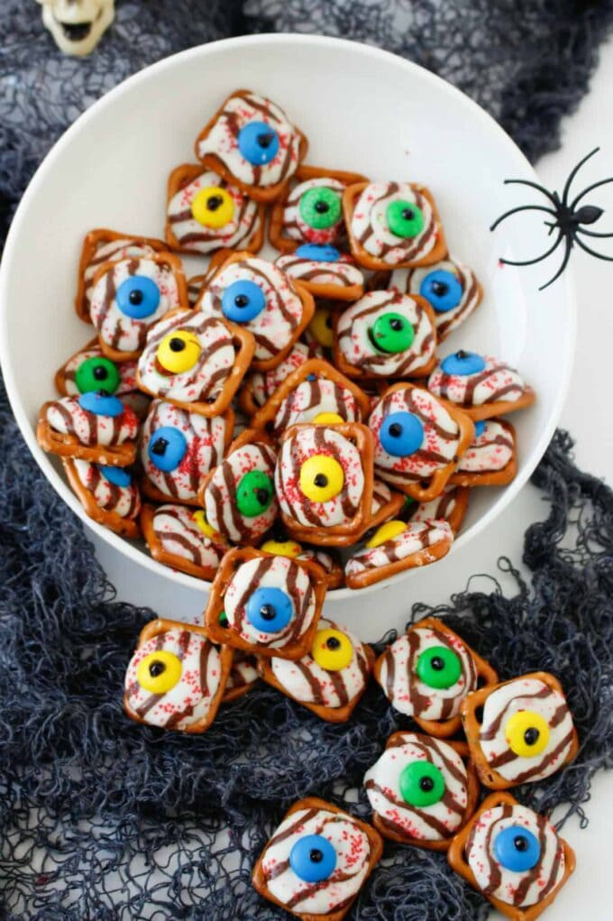 Halloween Pretzel Eyeballs in a white bowl with a spider