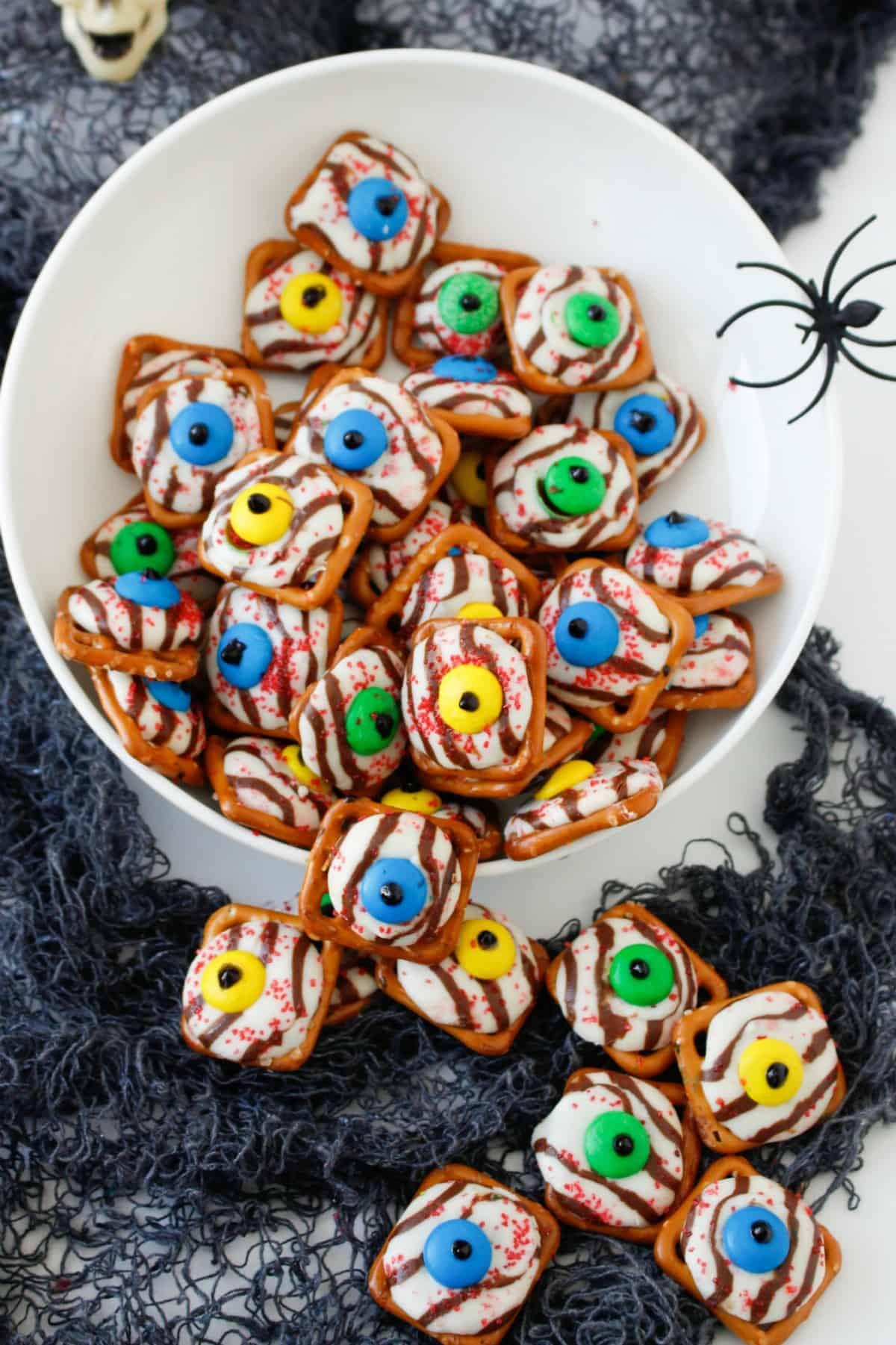 Halloween Pretzel Eyeballs in a white bowl with a spider