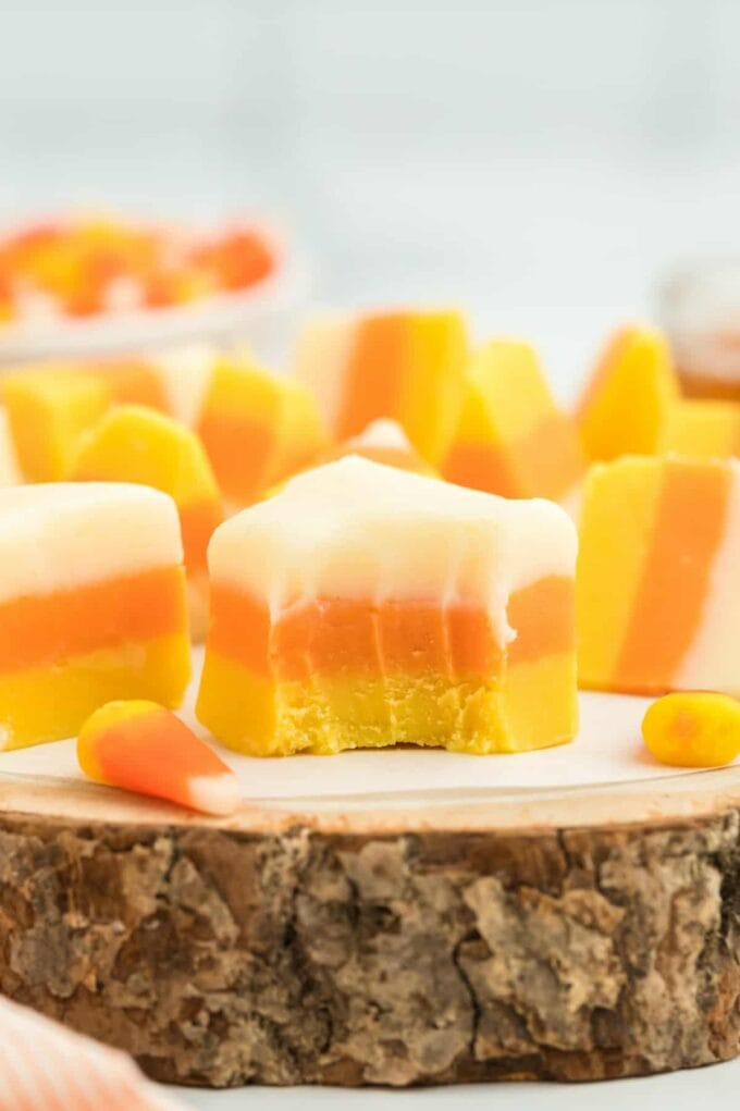 Candy Corn Fudge on a piece of wood with a bite out of one