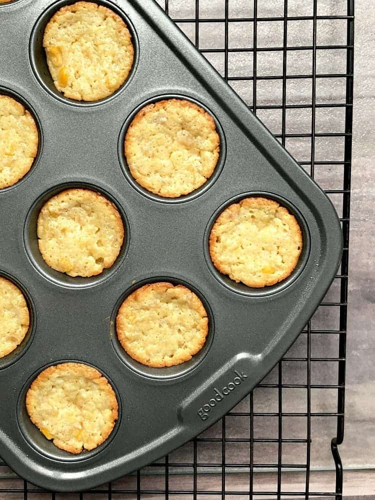 baked mini cornbread muffins in a muffin pan on a wire rack