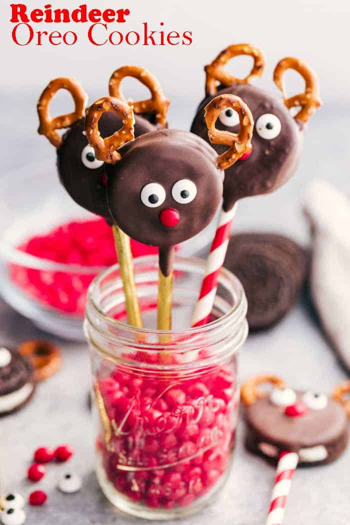 three reindeer oreo cookies standing in a jar filled with red hot candy.
