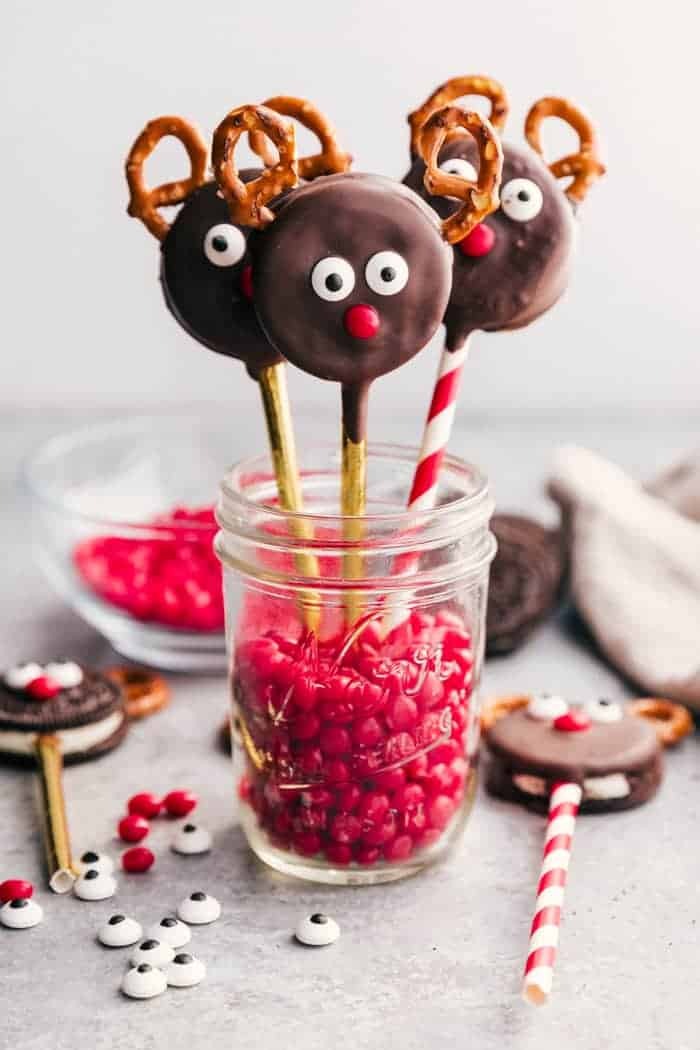 reindeer oreo cookies attached to lollipop stick and propped in jar of red hots.