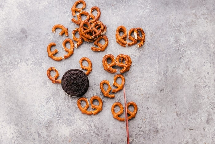 cutting pretzels to make antlers for reindeer oreo cookies