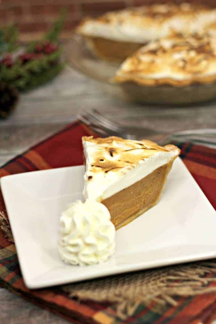 Sweet Potato Pie with Marshmallow Meringue on a white plate with whipped cream