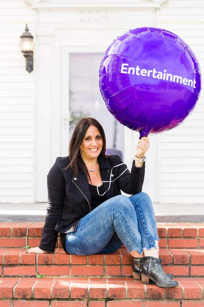 woman holding purple balloon with the word entertainment on it
