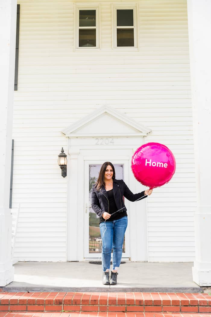 Woman holding pink balloon that say the words home on it