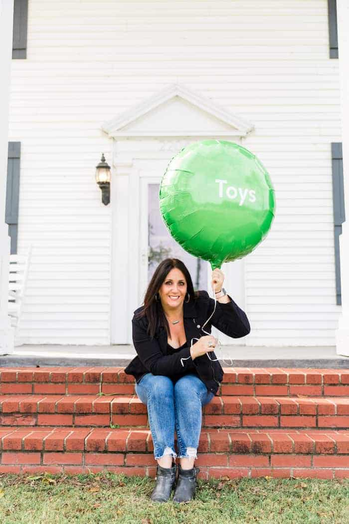 woman holding green balloon with the word toys on it