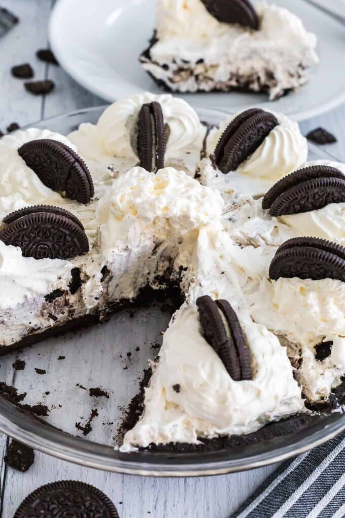 Oreo Pie with piece out and Oreos on top with whipped cream