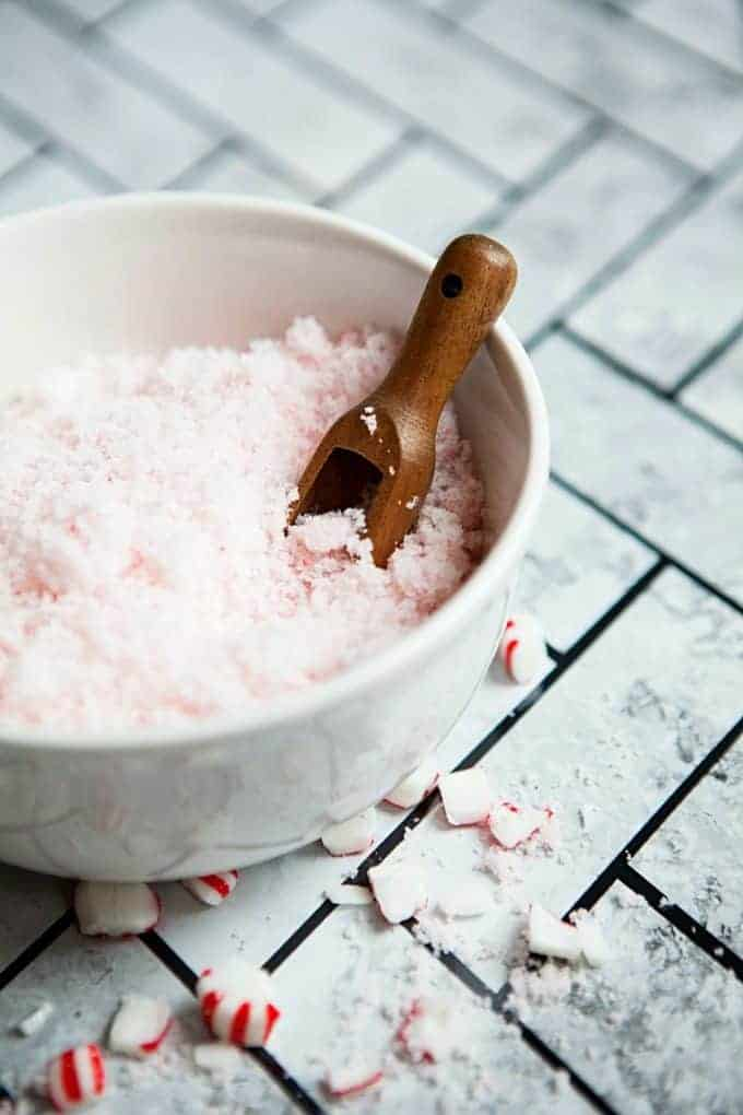 Peppermint Sugar Scrub in a white bowl with a wooden spoon