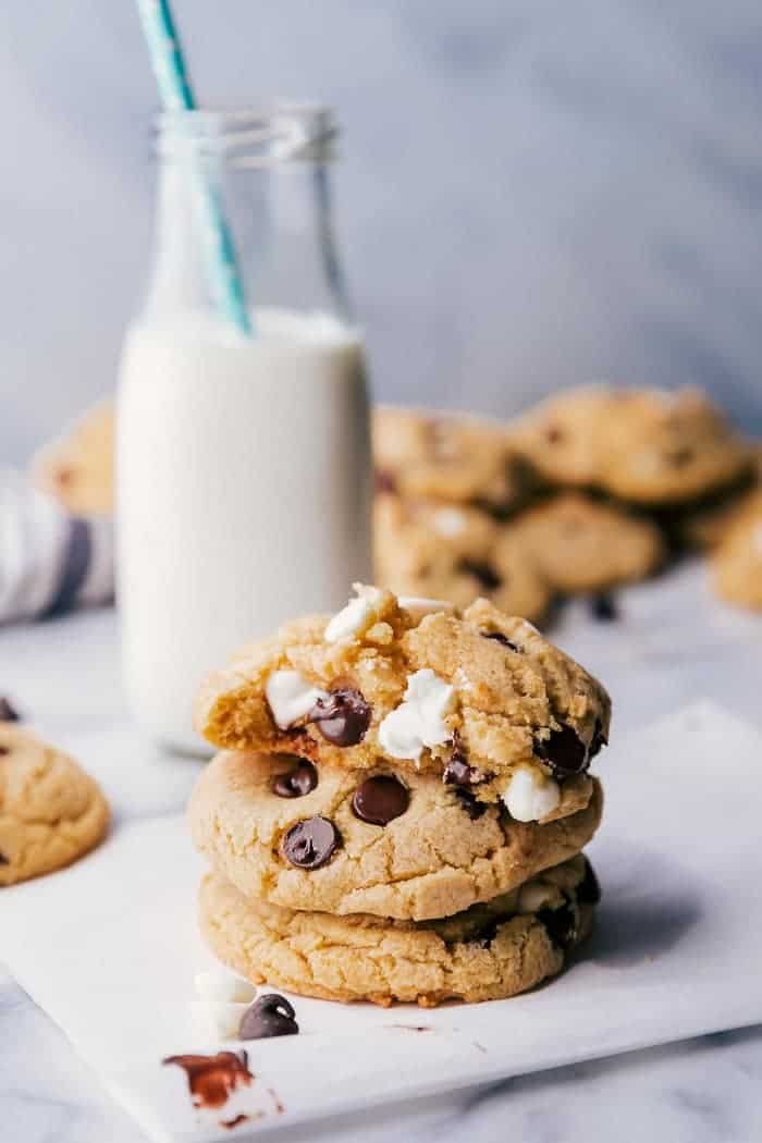 Chocolate chip cookies with pudding stacked on top of each other on a white background with a bite missing out of the top cookie, and a glass a milk served along side by Princess Pinky Girl