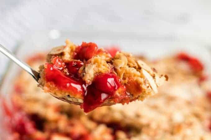 Bite of cherry dump cake on a spoon