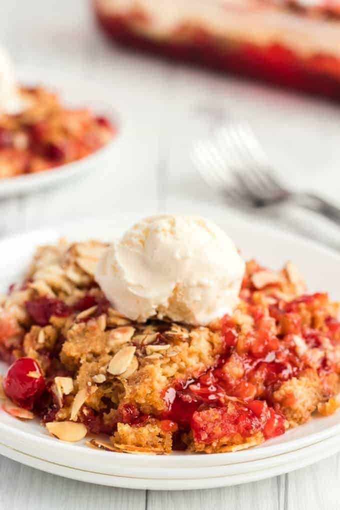 Cherry dump cake with vanilla ice cream on top on a white plate