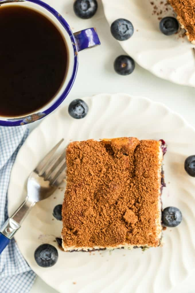Coffee Cake on a white plate with a cup of coffee and blueberries scattered