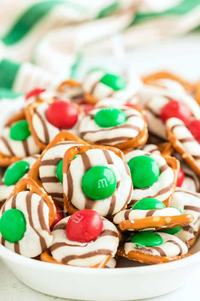 M&M Pretzel Hugs in a white bowl with green and red m&ms