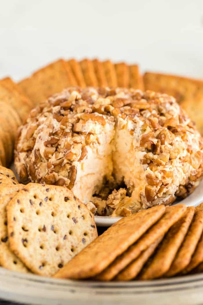 Cheese Ball with a slice out of it surrounded by crackers