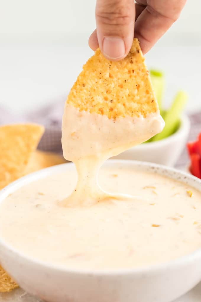 white queso dipping a chip