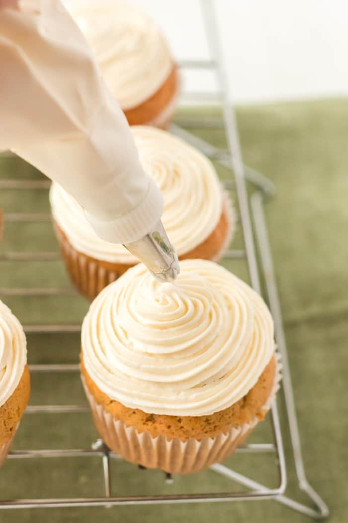 cupcakes being frosted with cream cheese frosting
