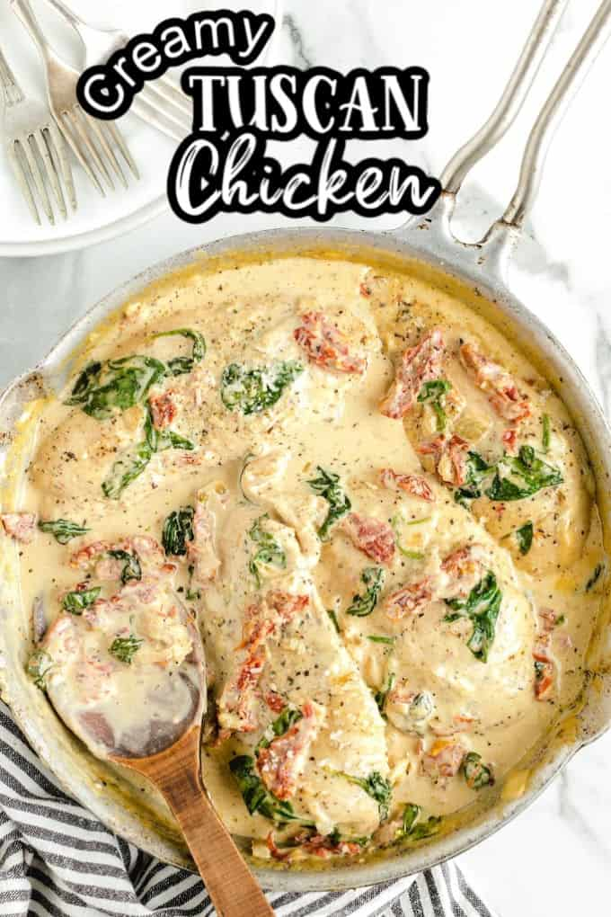Creamy Tuscan Chicken in a pot with a wood spoon