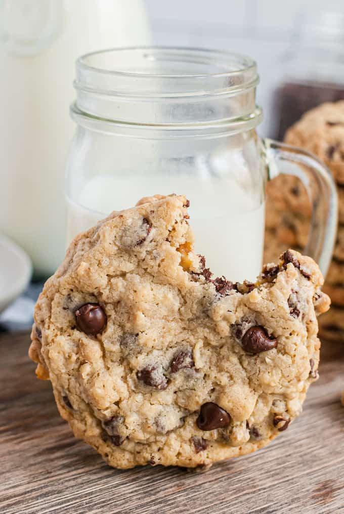Chocolate chip cookie with a bite taken out in front of a glass of milk in a mason jar
