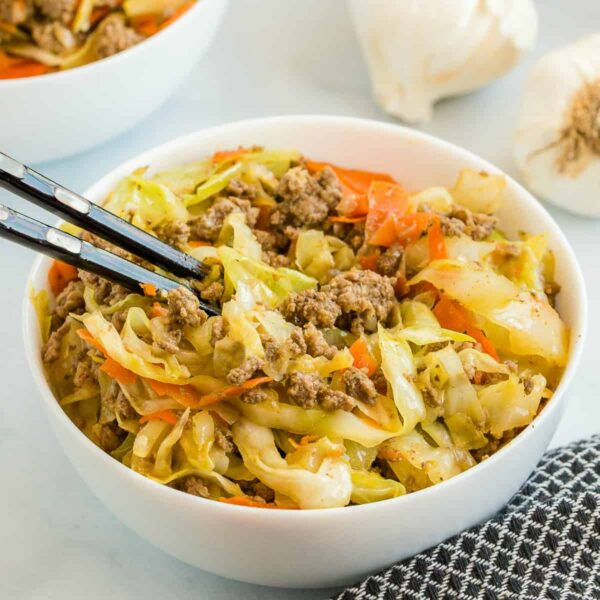 egg roll in a white bowl with black chopsticks