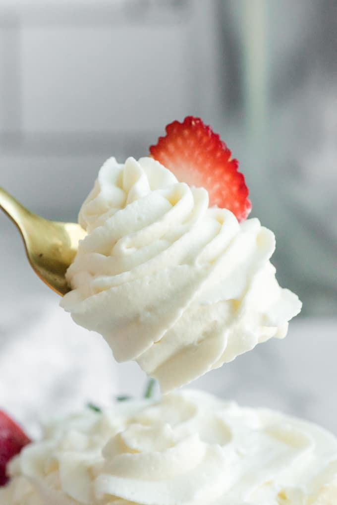 Stabilized Whipped Cream on a spoon with a sliced strawberry