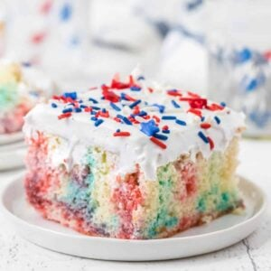 piece of red white and blue jello poke cake on a white plate square