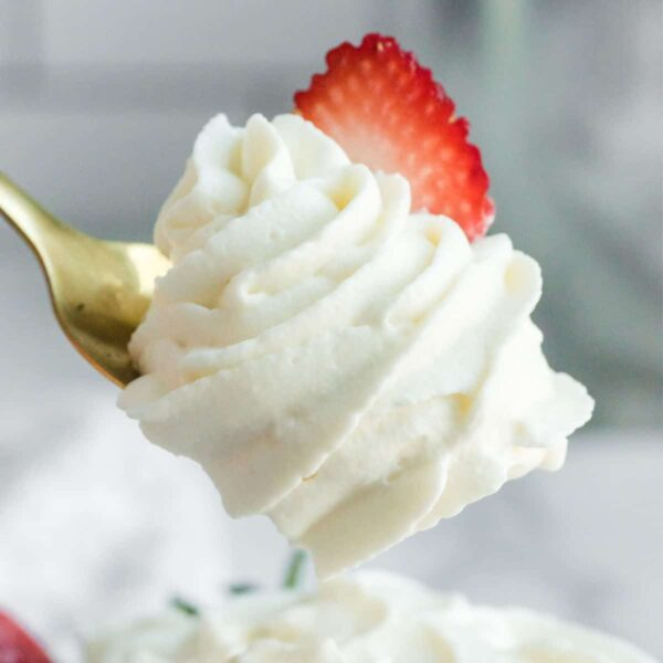 bite of whipped cream on a fork with a strawberry