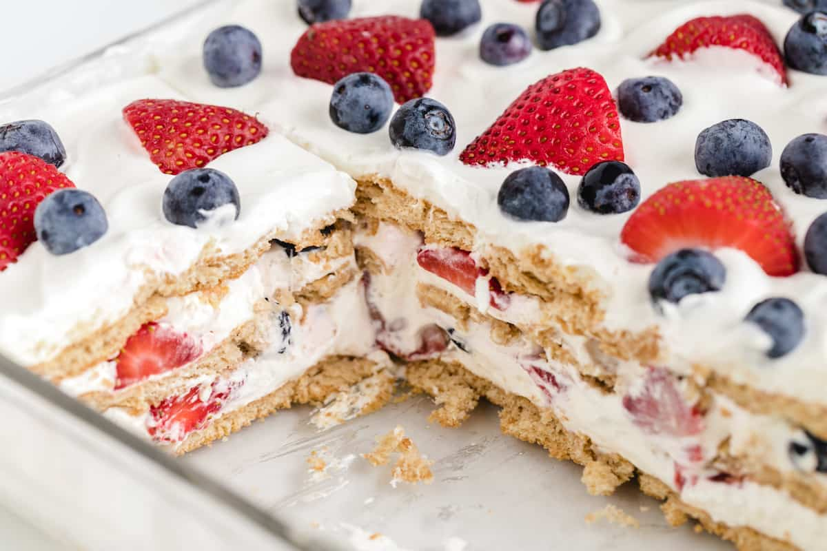 an icebox cake with blueberries and strawberries in a glass baking dish with a slice out of it