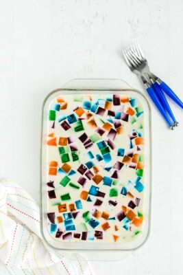 jello with different colored jello cubes with white gelatin mixture in a glass pan