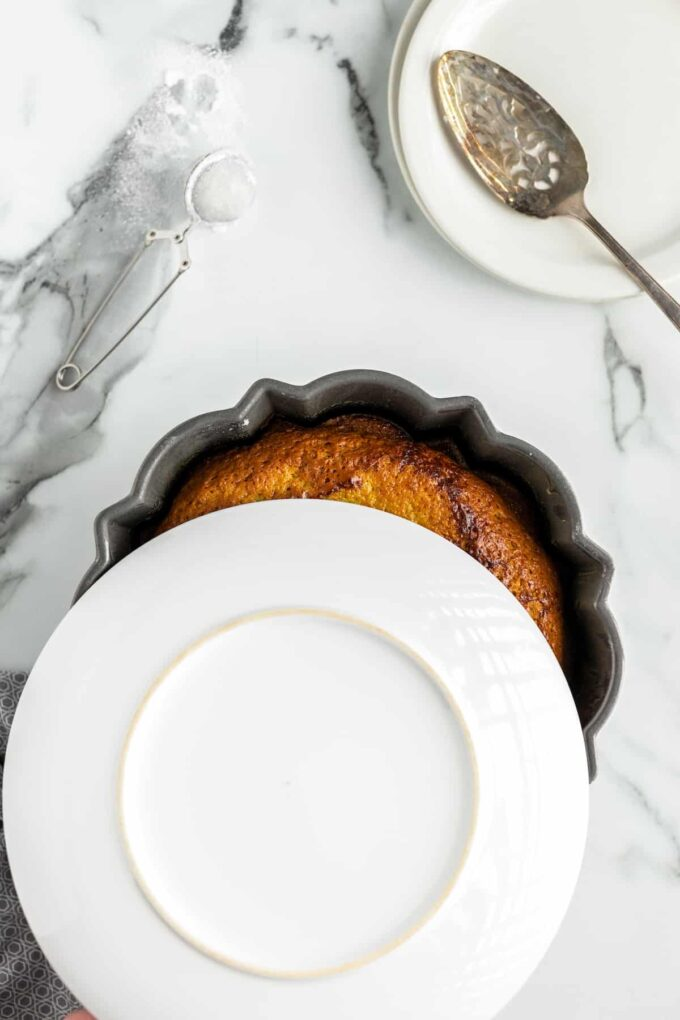 a white plate resting on top of a bundt pan with a cake in it