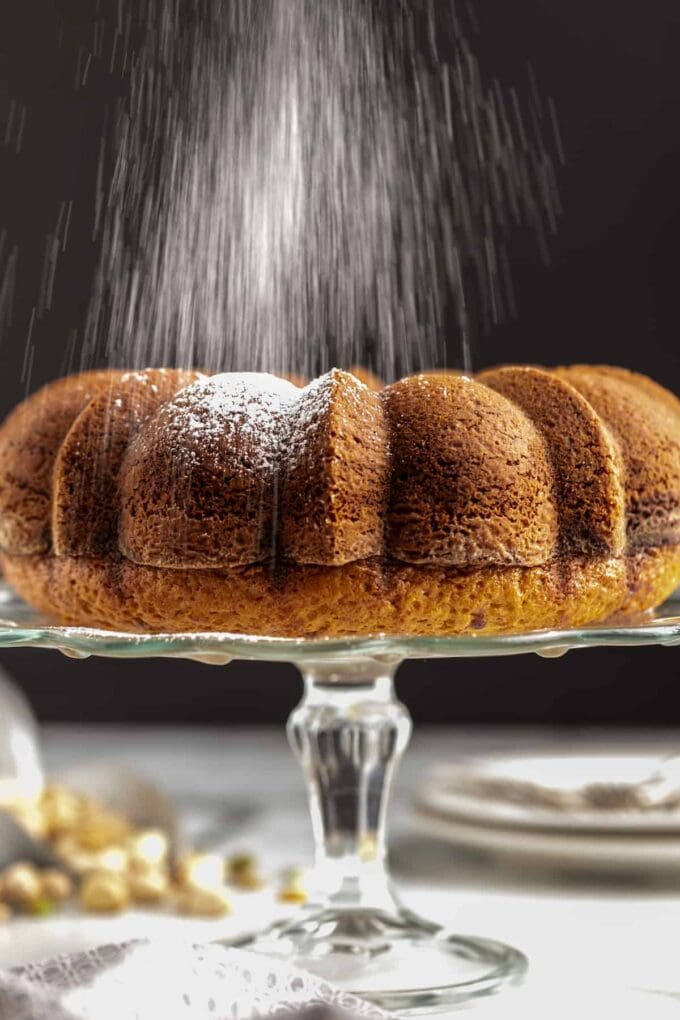 side view of a chocolate cake with powdered sugar being sprinkled on top of it