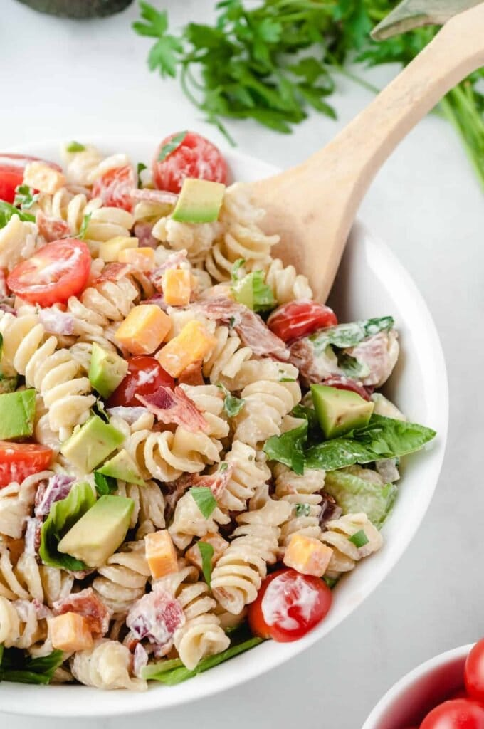 BLT Pasta Salad in a white bowl with a wooden spoon