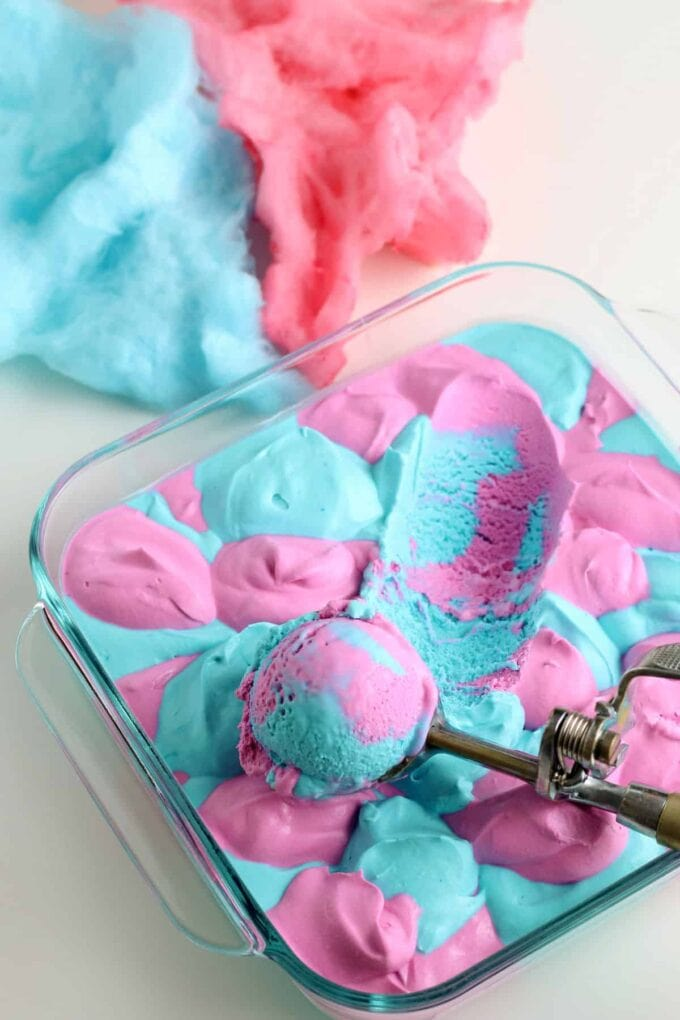 Cotton Candy ice cream being scooped in a glass dish with cotton candy in the background