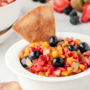 Fruit cut up in small pieces in a white bowl with a cinnamon chip
