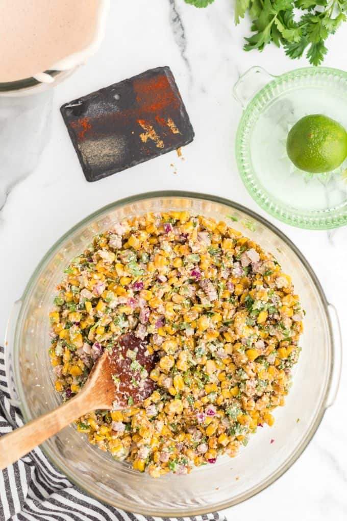 Mexican corn salad mixed up in a glass bowl