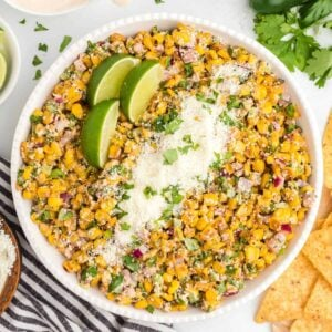 Mexican Corn salad in a white bowl with lime wedges and cheese on top