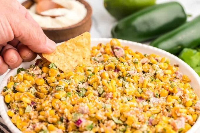 Mexican corn salad in a bowl being dipped with a tortilla chip